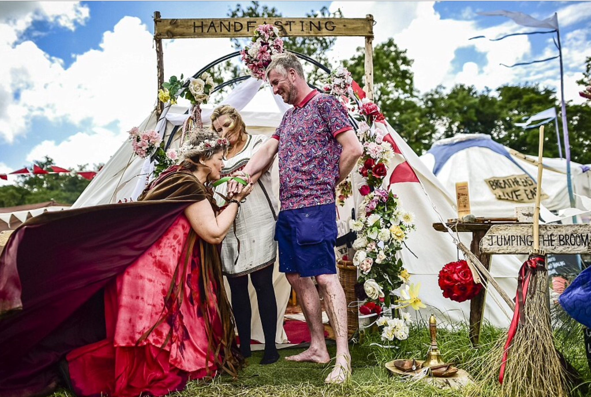 a couple at Glastonbury in casual clothes being hand fasted with green and pink ribbons by Glenda Procter of Cloud9Ceremonies