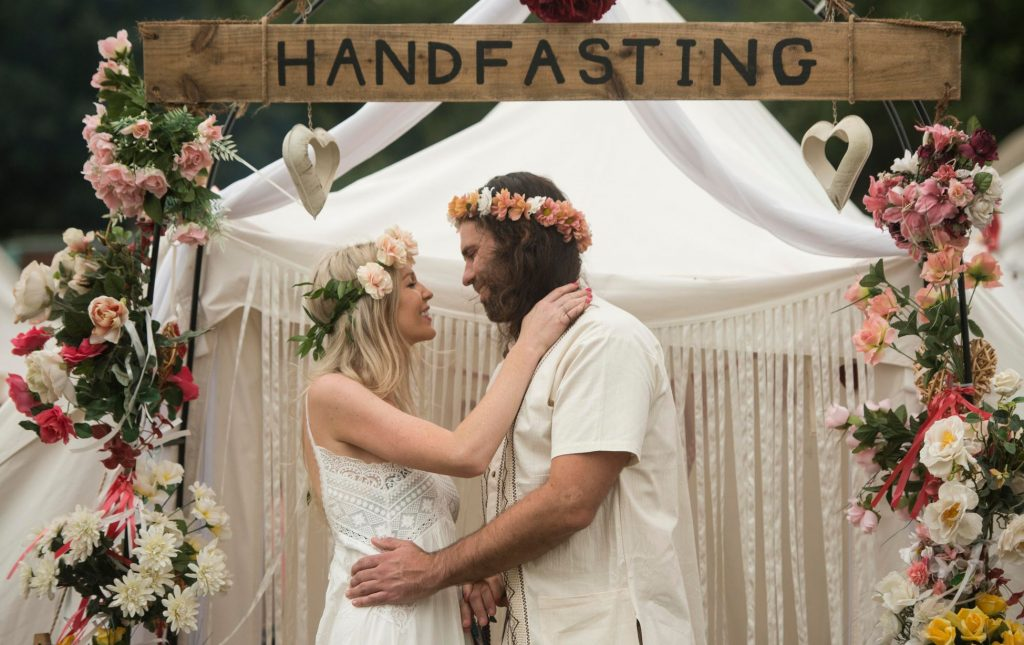 Couple wearing flower crowns at festival after handfasting commitment ceremony performed by Glenda Procter