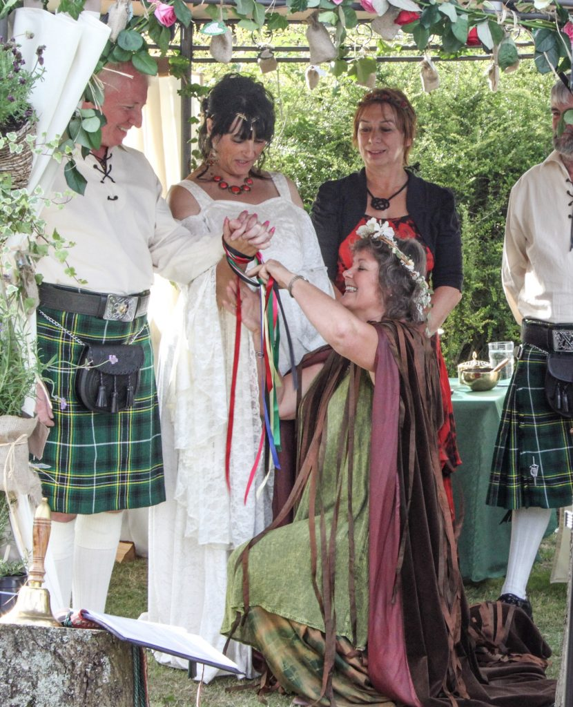 Celtic Handfasting of Bride and Kilted Groom under a wedding canopy as part of Wedding performed by Glenda Procter